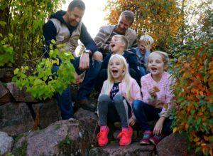 Glada barn med vuxna ute i naturen.
