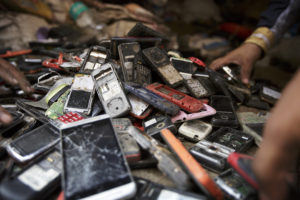 Workers sort through a pile of used mobile phones in New Delhi, India. Photographer: Kuni Takahashi/Bloomberg